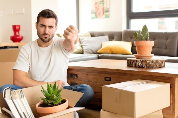 Мужчина сердится, злится, раздражается, разочаровывается или недоволен, показывает палец вниз с серьезным взглядом