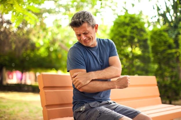야외에서 팔꿈치 통증을 느끼는 남자. 공원에서 벤치에 앉아 남자입니다. 의료 및 의학 개념