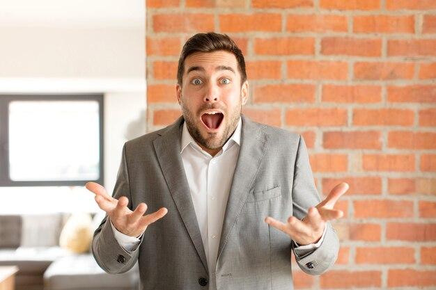 Мужчина чувствует себя чрезвычайно шокированным и удивленным, встревоженным и паническим, с напряженным и испуганным взглядом