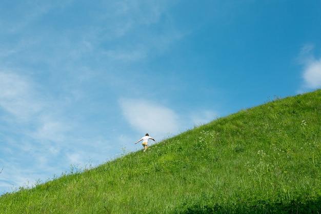 Человек, чувствующий себя счастливым и свободным, поднимается на зеленый холм в солнечный день.
