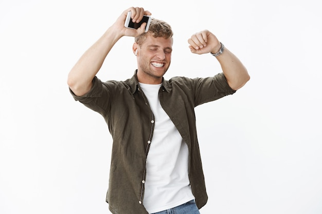 Man feeling happy and awesome dancing from joy with closed eyes and satisfied smile lifting hands holding smartphone wearing wireless earbuds, listening music carrying away with good song vibes