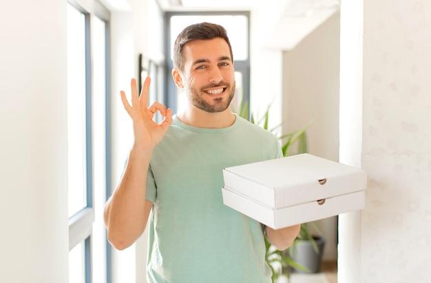 Мужчина чувствует себя счастливым, расслабленным и довольным, демонстрирует одобрение жестом ок, мужчина улыбается