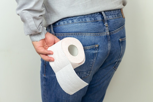 Man feeling pain and holding toilet paper roll close-up. diarrhea, hemorrhoids or constipation concept