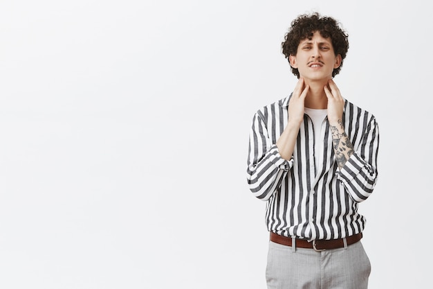 Man feeling pain in throat might getting cold. uncomfortable curly-haired guy with moustache and tattoos in striped shirt raising head clenching teeth and frowning touching neck having discomfort