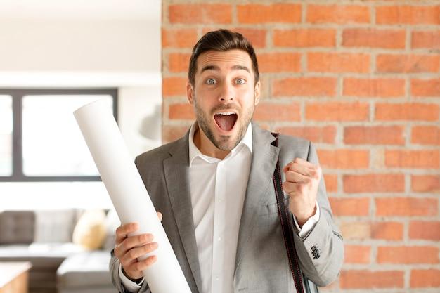Мужчина потрясен, взволнован и счастлив, смеется и празднует успех, говоря: