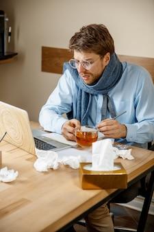 気分が悪くて疲れている男。自宅でカップを持って働いている男性、ビジネスマンは風邪、季節性インフルエンザにかかった。