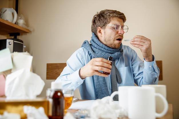 Человек чувствует себя больным и усталым. человек с чашкой работает дома, бизнесмен простудился, сезонный грипп.