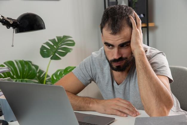 Человек чувствует себя усталым, работая дома на ноутбуке