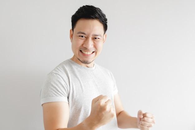 남자는 흥분된다. 남자는 회색 바탕에 회색 티셔츠를 입는다.