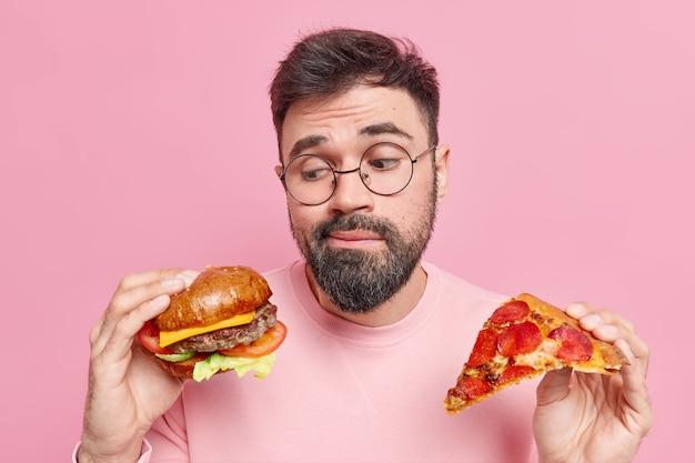 男はハンバーガーを食べるかピザを食べるかをためらうと感じますジャンクフードを食べることを好む丸い眼鏡とジャンパーを着ています