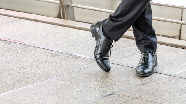 Man feet in black leather shoes stands on concrete floor.