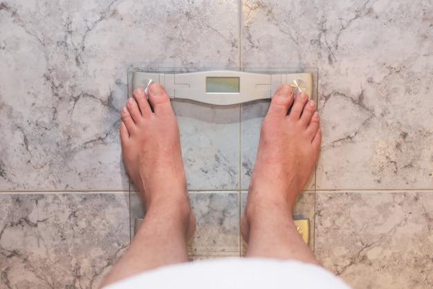 체중 규모에 서있는 남자 발