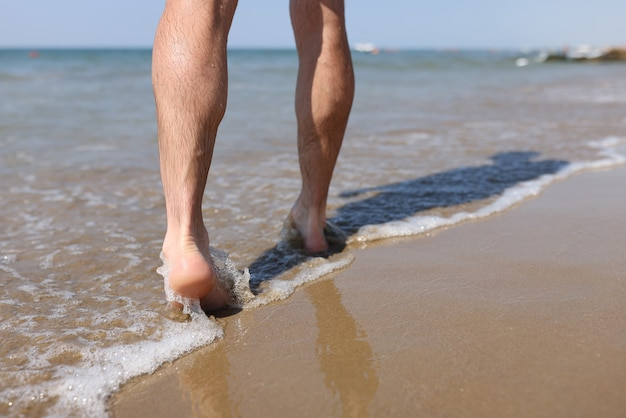 모래 해변 근접 촬영을 따라 걷는 남자 발