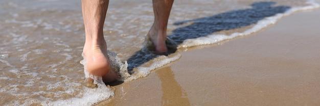 Man feet walking along sandy beach closeup