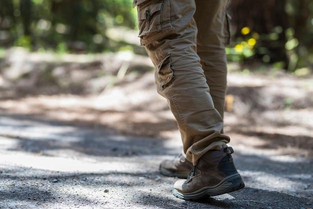 夏に森の小道を歩くハイキングシューズを履いた男の足、歩道を歩く男。ラフな歩道で靴を履いてハイキングする男性の低いセクション