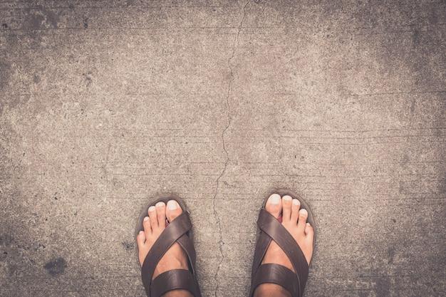Man feet wearing some brown flip flops standing on the asphalt concrete floor