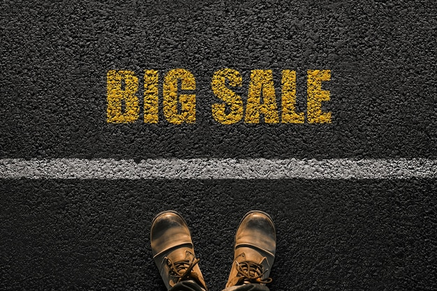 Man feet with leather shoes walks near the line with the yellow text big sale on the pavement, top view. sales and marketing concept. step into shopping