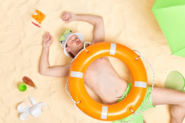 Man fell asleep at beach lies on warm white sand with lifebuoy on stomach enjoys summer travel holiday has lazy day surrounded by slippers parasol refreshing drink tennis raquet