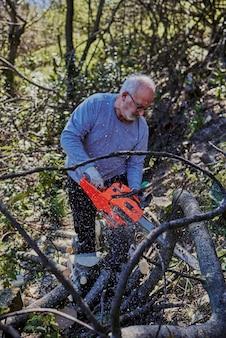 Человек рубит лес с помощью электрической бензопилы
