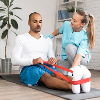 Man and female physiotherapist doing exercises
