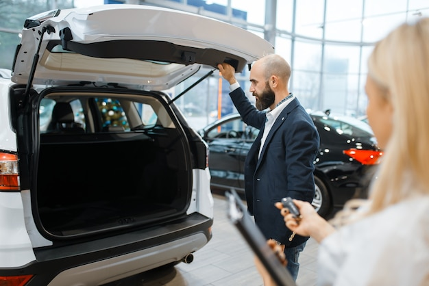 Man and female seller looking auto in car dealership.