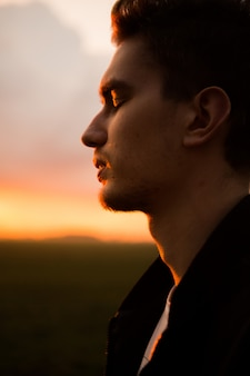 Man in field on beautiful sunset. silhouette of young man in the nature
