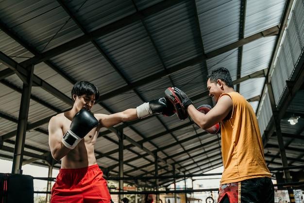 권투 훈련 캠프에서 펀치 패드와 함께 남자 전투기와 코치 훈련. 그녀의 코치와 함께 펀치 운동을 하 고 권투 장갑에 남자