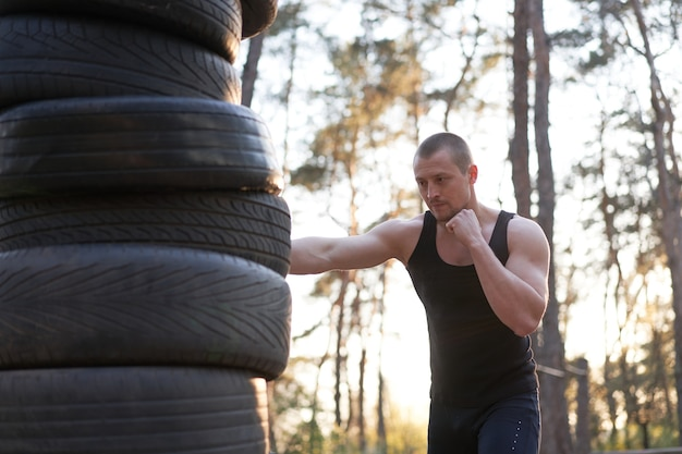 Man fighter training boxing outdoor tire diy handmade gym in forest fitness workout. young adult  training right hand hit nature without boxing gloves. sportive activie male healthy lifestyle concept.