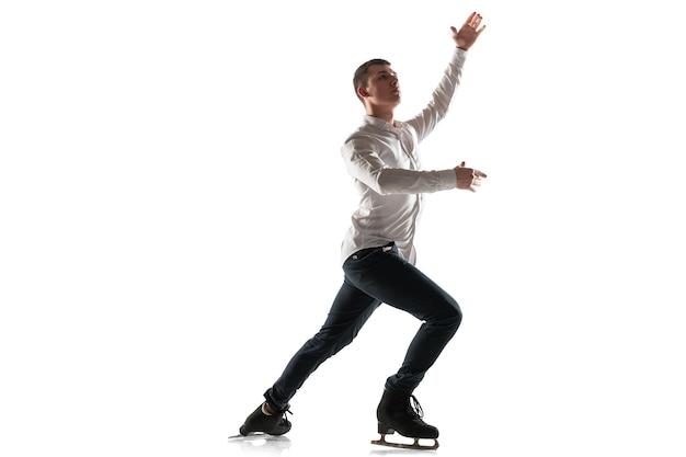 コピースペースと白いスタジオの壁に分離された男のフィギュアスケート。氷上でのアクションとモーションのプロの練習とトレーニング。優雅で無重力。動き、スポーツ、美しさの概念。