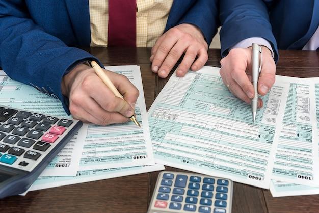 計算者との人の記入と会計財務文書税フォーム1040。税金の時間