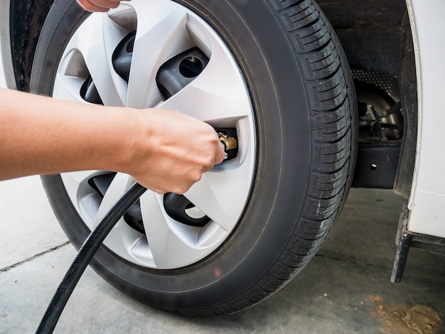 Man filling air pressure in the car tyre close up