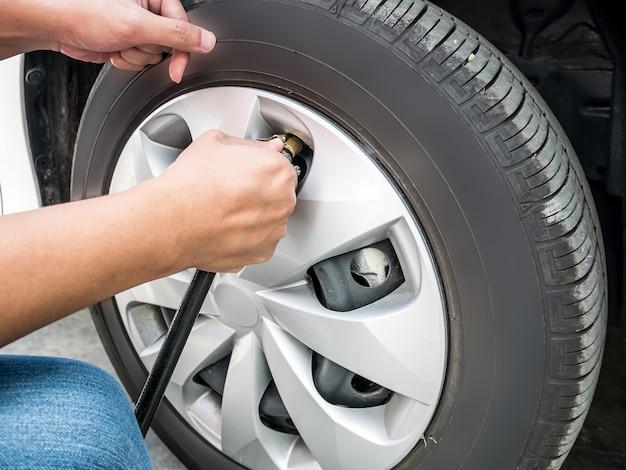 車のタイヤの空気圧を埋める男がクローズアップ