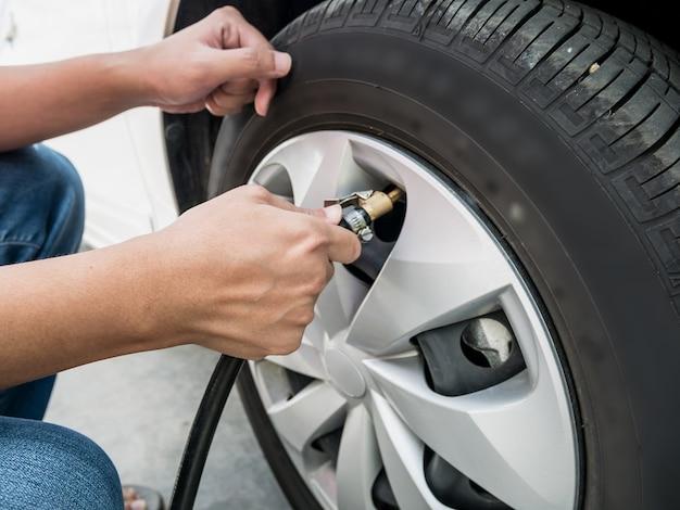 車のタイヤの空気圧を充填する男をクローズアップ