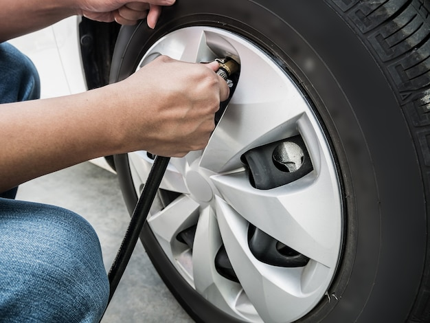 Человек заполняет давление воздуха в автомобильной шине