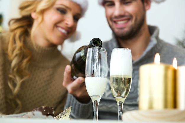 Uomo che riempie bicchieri di champagne