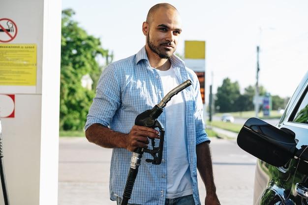 Человек заправляет бензин в машине на азс