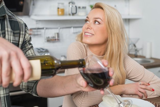 Man filling glass by wine from bottle near cheerful woman in kitchen