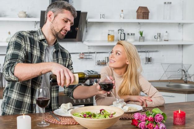 Man filling glass by wine from bottle near woman in kitchen