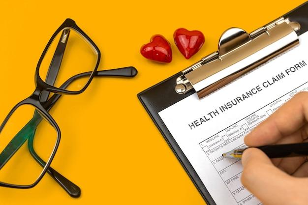 건강 보험 청구 양식을 작성하는 남자. 노란색 바탕 화면에 클립보드, 펜 및 빨간색 하트가 있는 비즈니스 바탕 화면. 상위 뷰 사진
