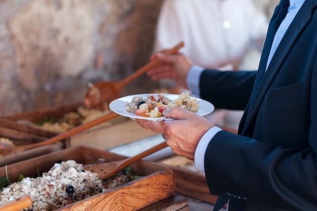 男は彼の皿にスプーンで木製トレイにサラダを充填