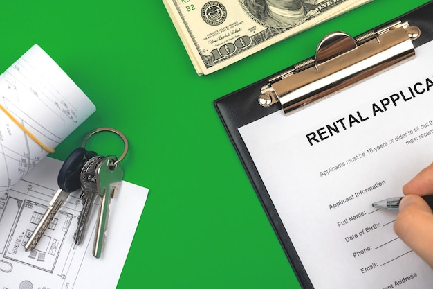 Человек, заполняющий договор об аренде. буфер обмена с официальной формой заявки. стол с деньгами и ключами от дома. зеленый фон фото