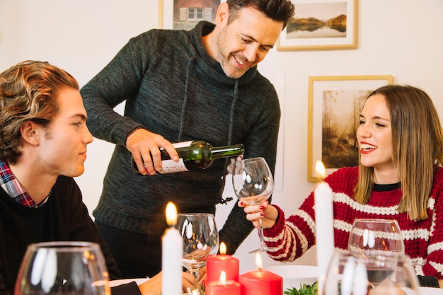 Man filling wine glass at christmas dinner