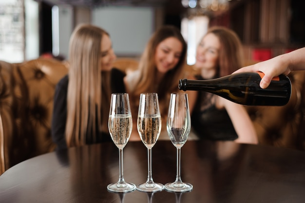 Man fills glasses of champagne for three beautiful young women in restaurant