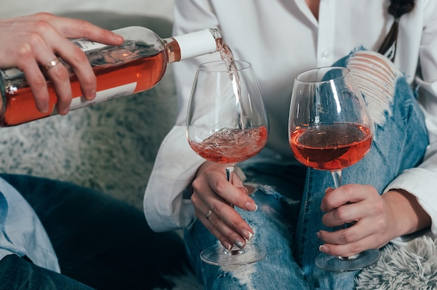 A man fills glasses with rose wine
