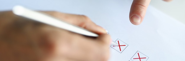 A man fills test columns with a red pen
