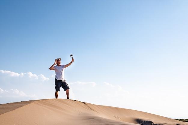 Мужчина снимает себя на мобильный телефон в дюнах пустыни. создатель контента для путешествующих мужчин