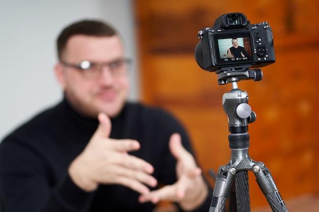 オンラインフォロワーのために三脚を使用してカメラでビデオブログを撮影する男。ソーシャルメディア、インフルエンサー、新技術、インターネットのコンセプト