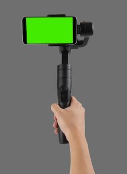 灰色の壁に隔離されたジンバルスタビライザーを使用して空白の画面のスマートフォンで撮影する男
