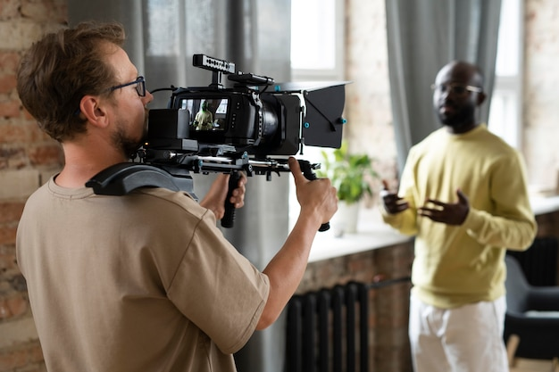 Uomo che filma con una telecamera professionale per un nuovo film