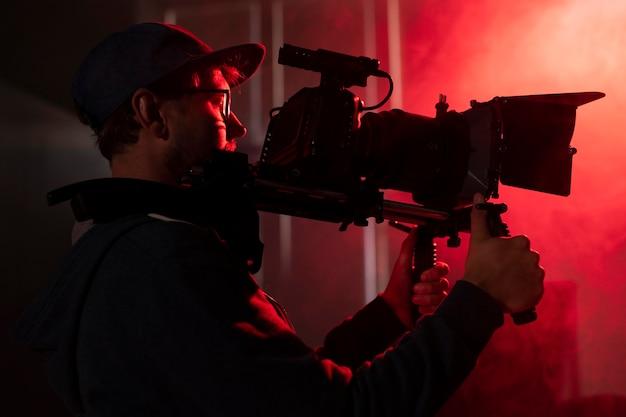 Uomo che filma con una telecamera professionale